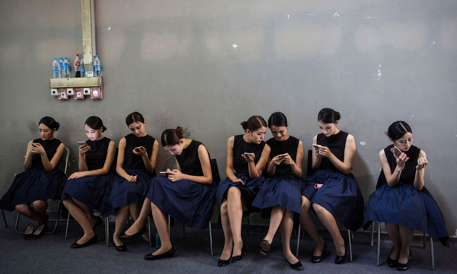 Exhibit hostesses using smartphones during the China (Guangzhou) International Automobile Exhibition