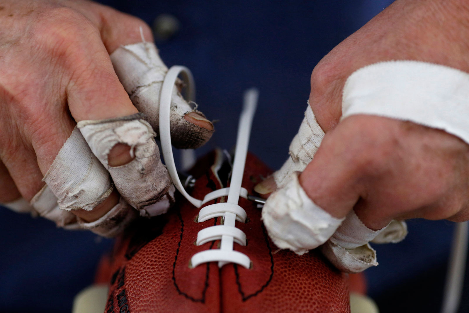 A worker installs laces on a football at the Wilson Sporting Goods factory in Ada, Ohio