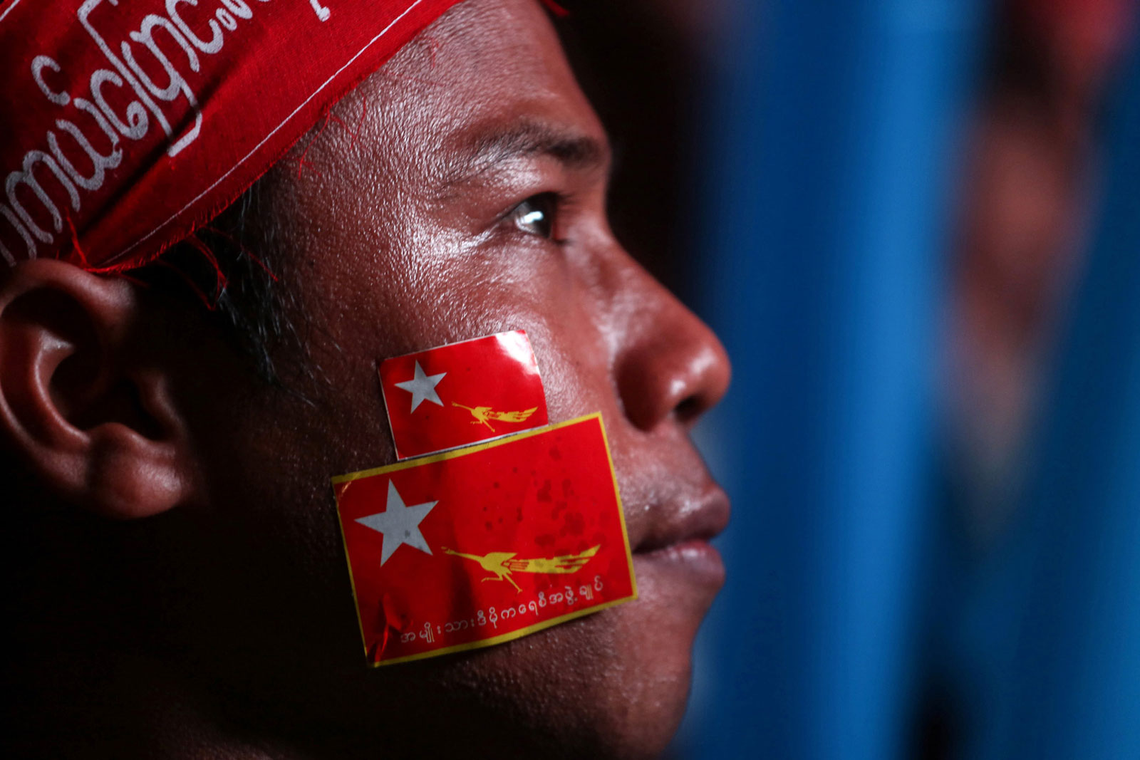 A National League for Democracy party supporter looks on during celebrations of election results outside the party headquarters in Yangon, Myanmar