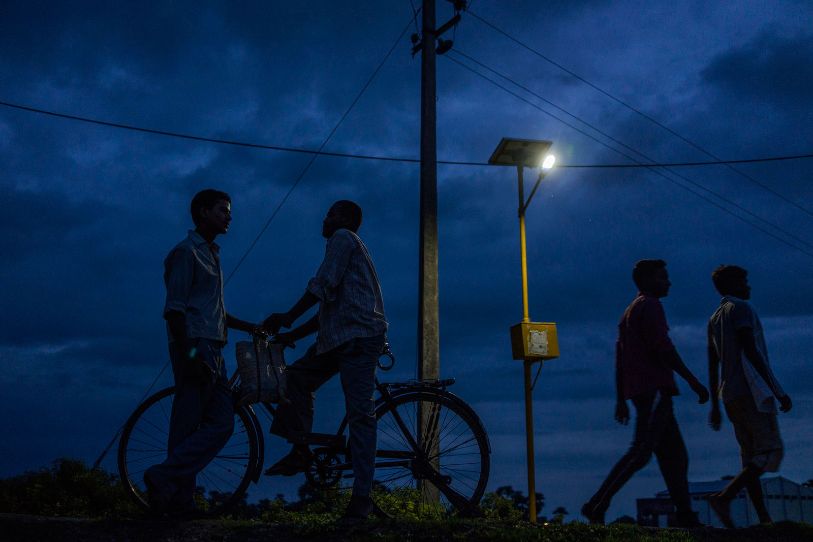 People walk past a light powered by energy from a solar-power microgrid at night in the village of Dharnai in Jehanabad, Bihar, India