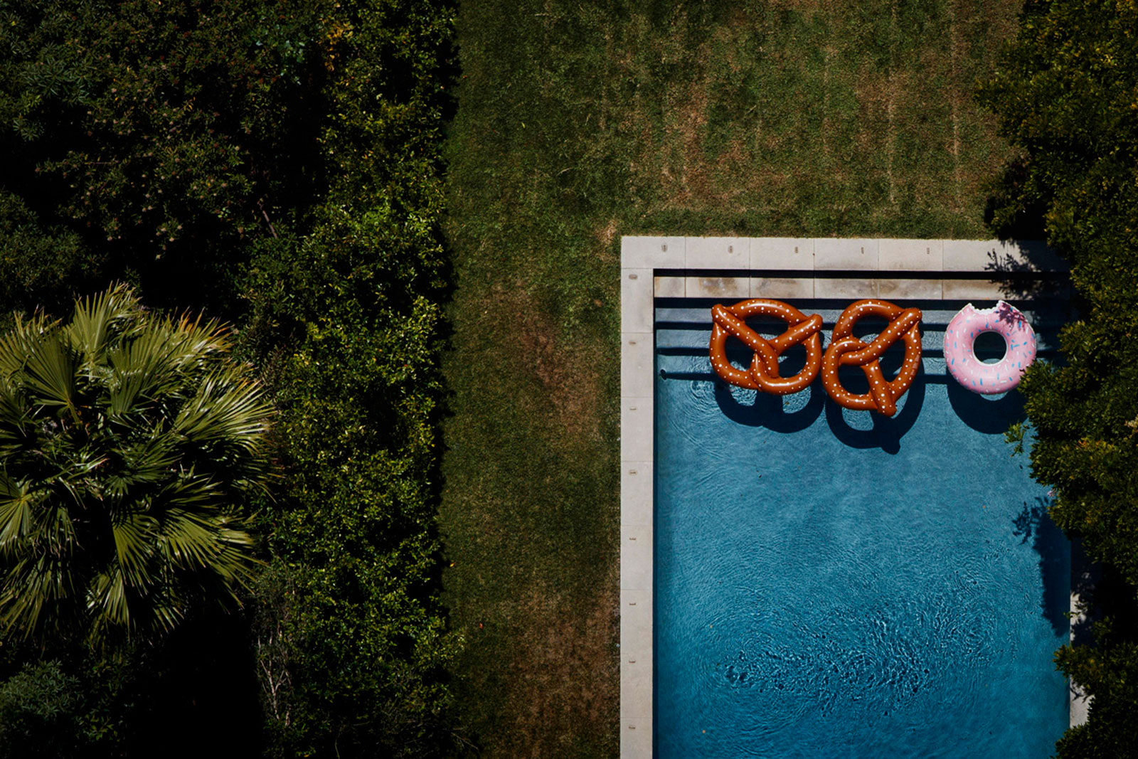 Inflatable pretzels and a doughnut float in a backyard pool at a home off Summit Drive in Los Angeles
