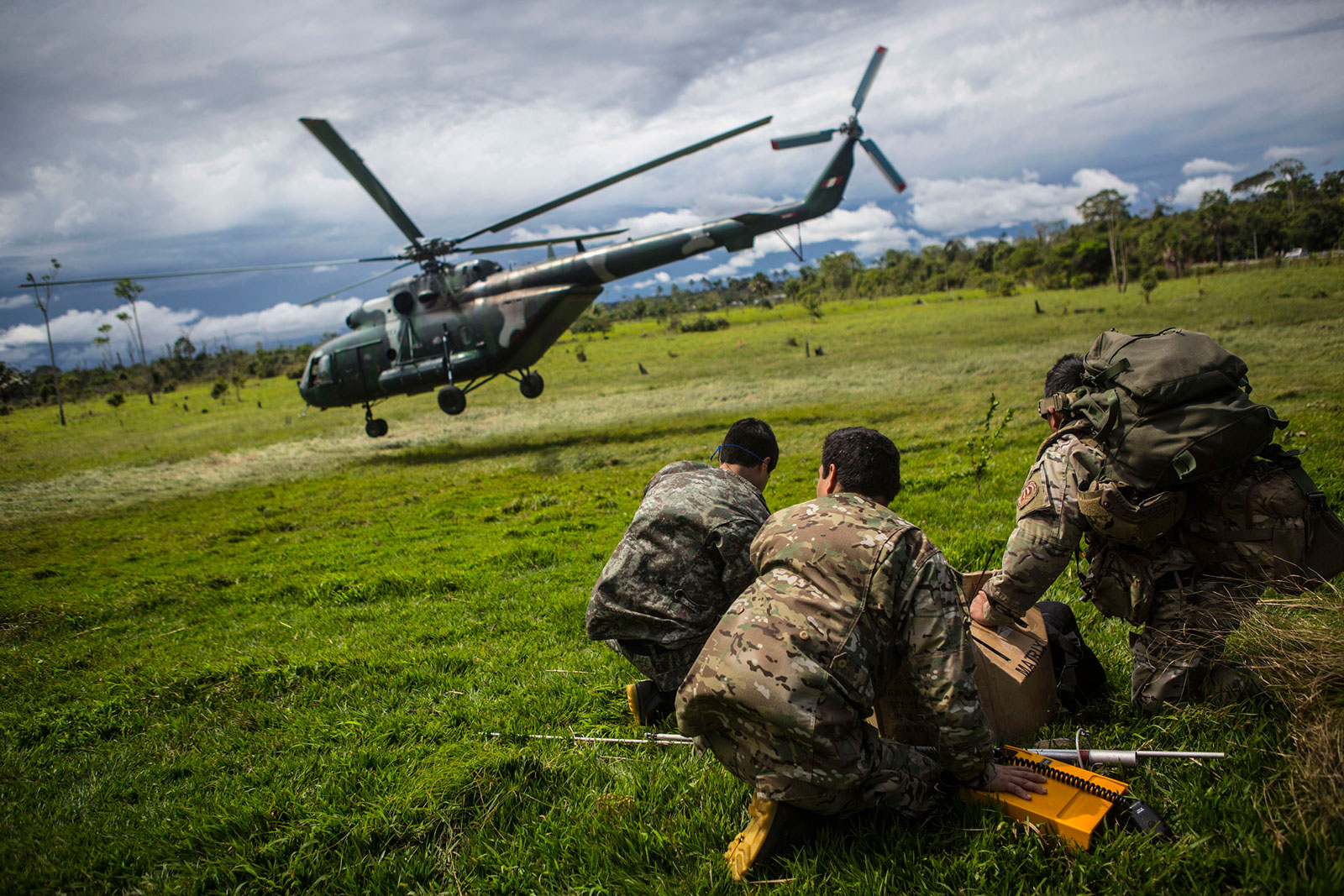 Police officers look on as a helicopter loaded with supplies and crew flies out to raid an illegal gold mining camp inside the Amazonian National Reserve buffering zone of Tambopata in Puerto Maldonado, Peru