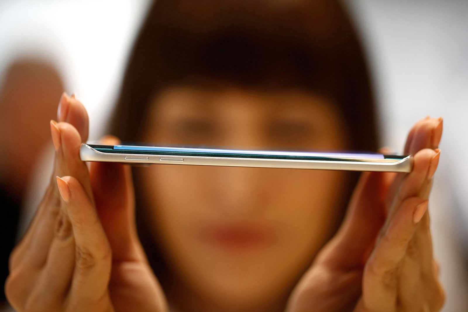 An employee shows the curved screen of a new Galaxy S6 Edge smartphone at a Samsung Electronics news conference ahead of the Mobile World Congress in Barcelona
