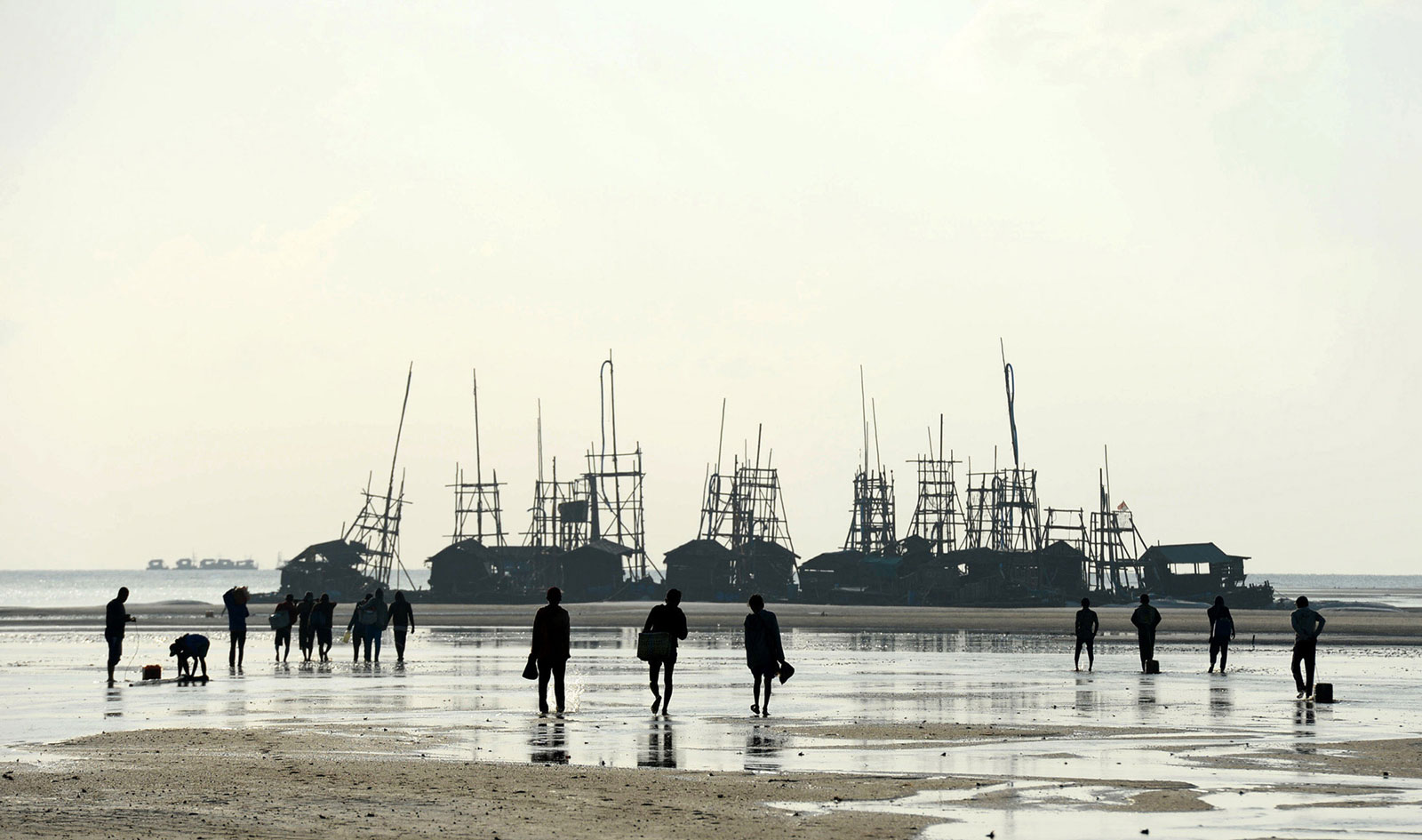 Workers walk toward wooden dredging rafts on the beach off the coast of Bangka Island, Indonesia