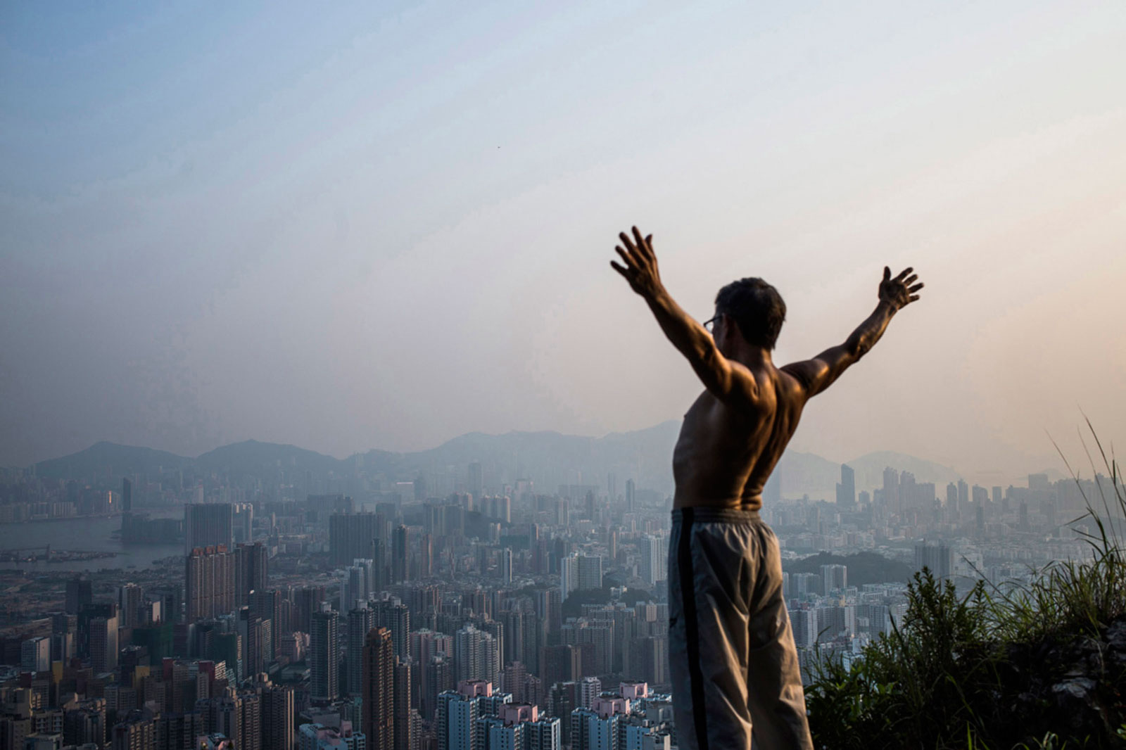 A man stretches as buildings rise in the background in Hong Kong
