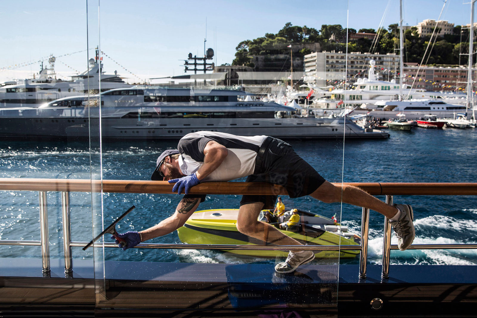 A crew member cleans windows aboard superyacht Solandge, built by Germany's Lürssen Werft and moored at the Monaco Yacht Show in Port Hercules, Monaco