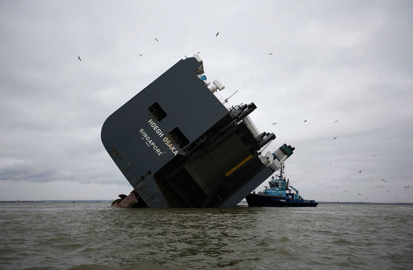 The Lomax firefighting tug, operated by Solent Towage, sits alongside the Hoegh Osaka ro-ro cargo ship, operated by Hoegh Autoliners, as it sits grounded on Bramble Bank in the Solent near Cowes, on the Isle of Wight, U.K.