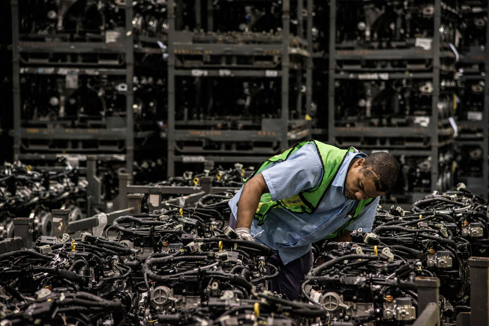 An employee performs a quality-control inspection on the assembly line at the Ford Motor engine manufacturing facility in Camacari, Brazil, on Monday, July 27, 2015.