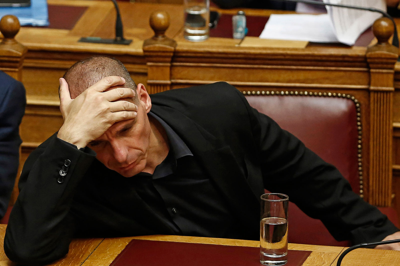 Yanis Varoufakis, Greece's finance minister, speaks to a lawmaker at the Greek Parliament