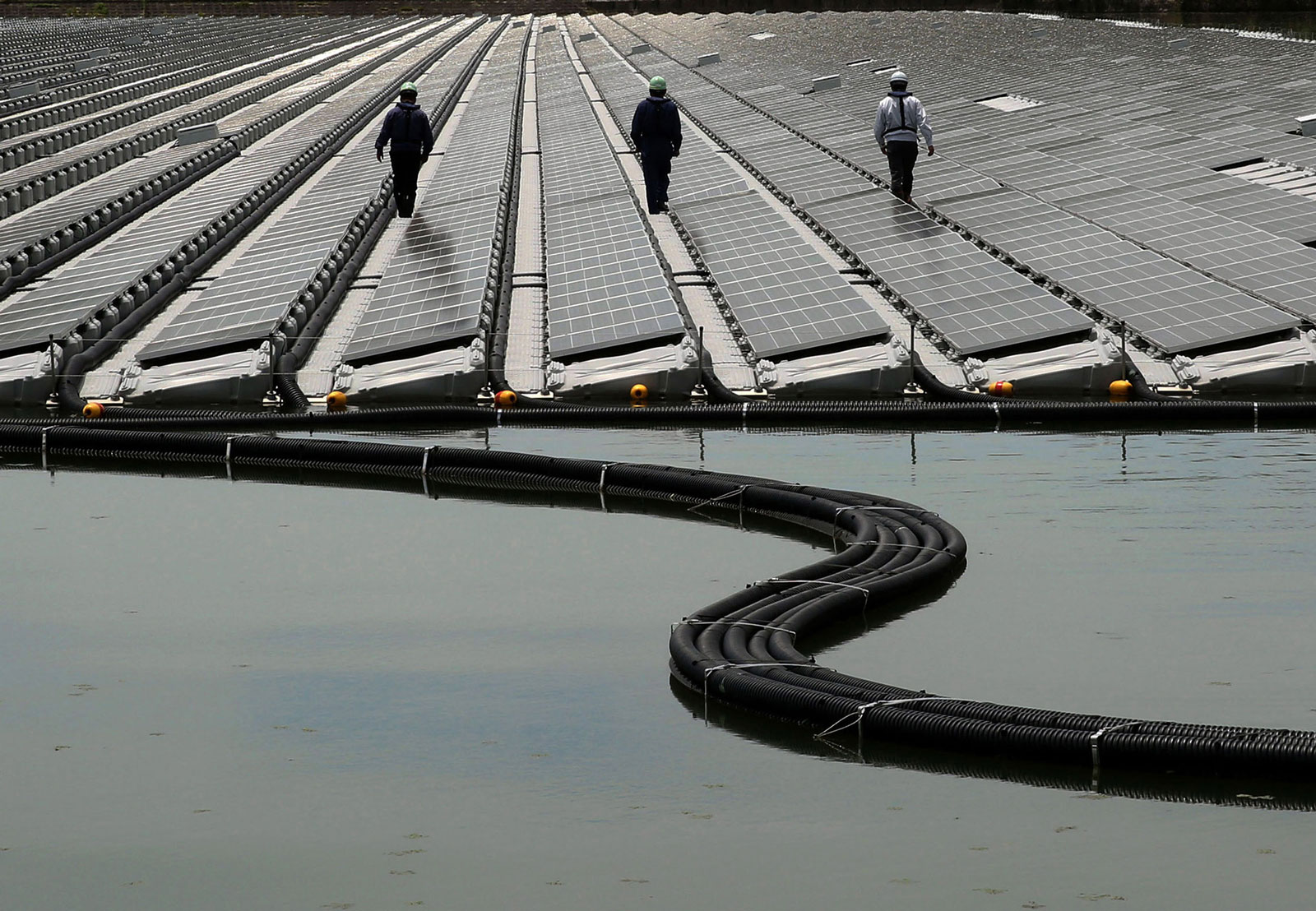 Workers walk between rows of solar panels at the 2.3-megawatt floating solar power station operated by Kyocera TCL Solar