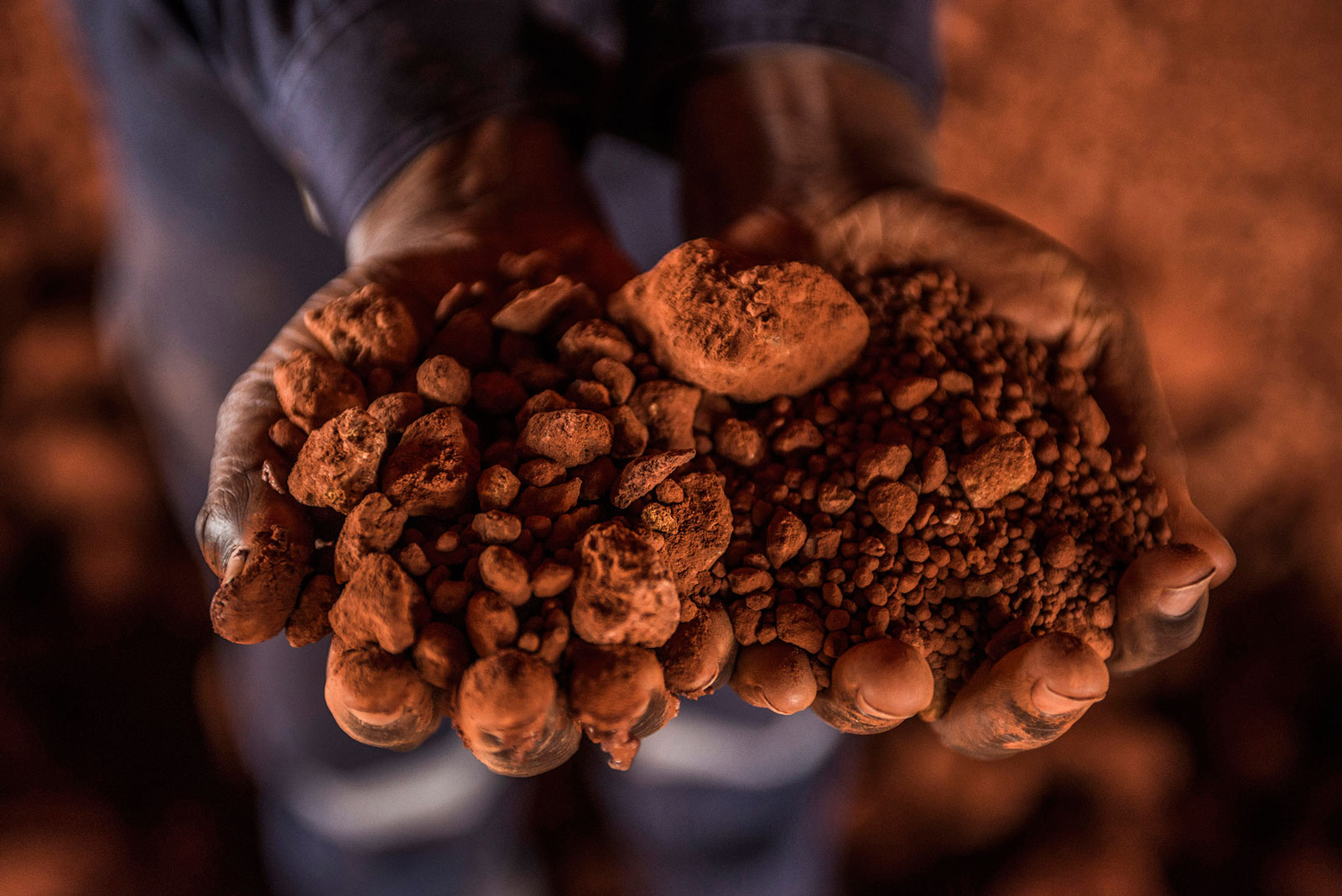 A worker holds crushed bauxite in a storage building at a treatment plant operated by Compagnie des Bauxites de Guinee in Kamsar, Guinea