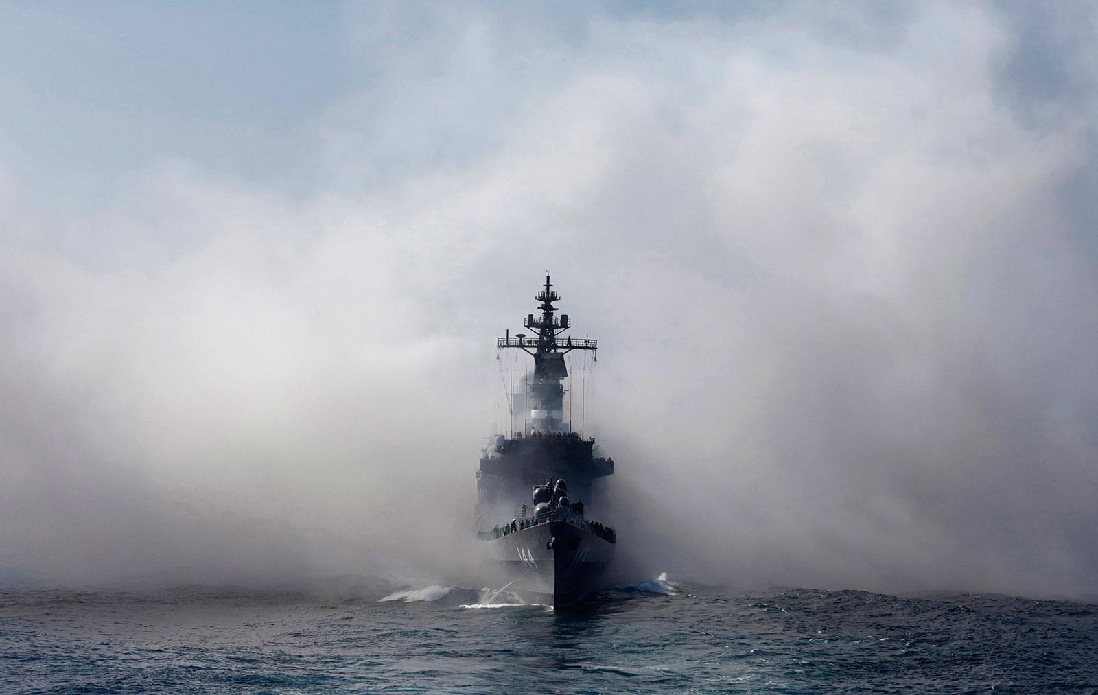 Japan Maritime Self-Defense Force destroyer ship Kurama sails as it exits the smoke of anti-IR missile flares during a review at Sagami Bay, off Yokosuka, Kanagawa Prefecture, Japan