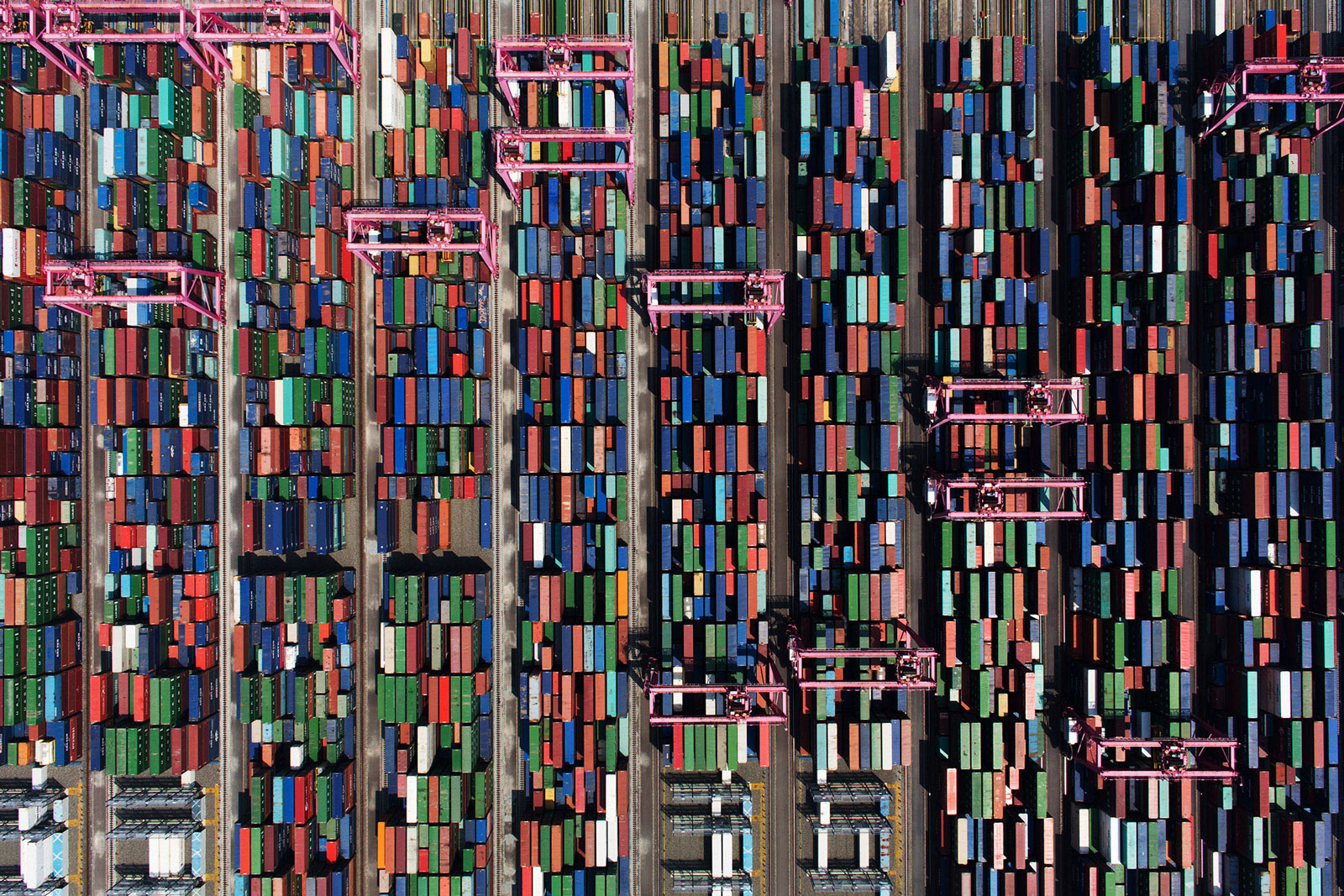 Shipping containers sit stacked among gantry cranes at the BNCT container terminal at Busan New Port in Busan, South Korea