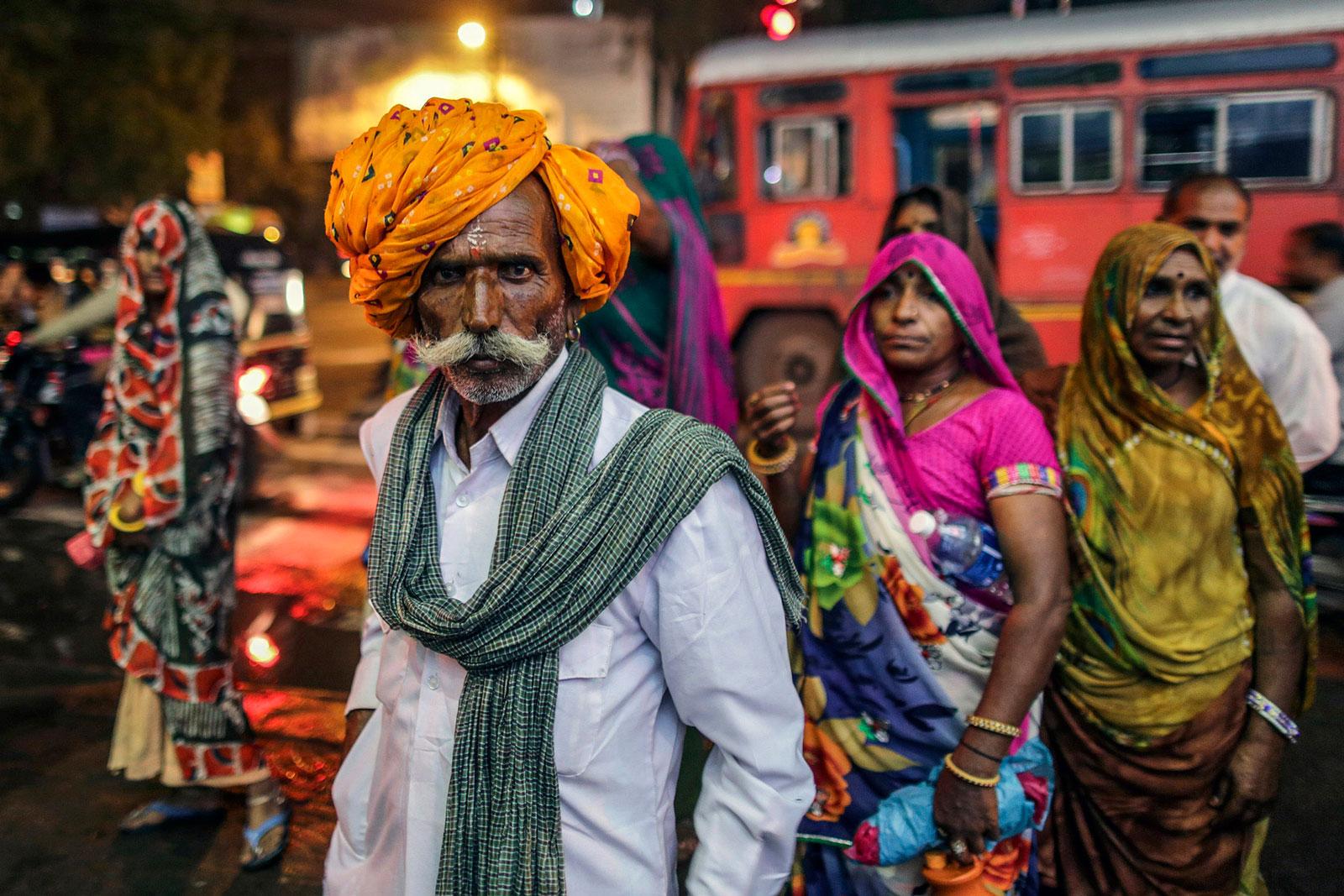 A Hindu pilgrim poses for a photograph near a bus stop in Nashik, Maharashtra, India