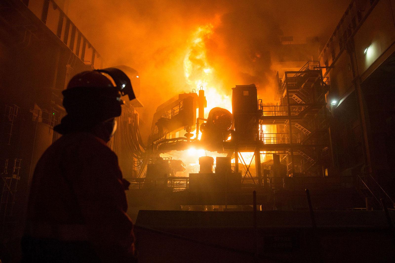 An employee looks on as a ladle is emptied in a steel mill plant at the Celsa Steel UK steel mill in Cardiff, U.K.