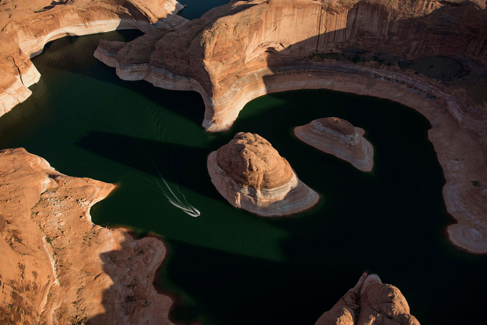 A boat moves along the shore of Lake Powell in Page, Ariz.