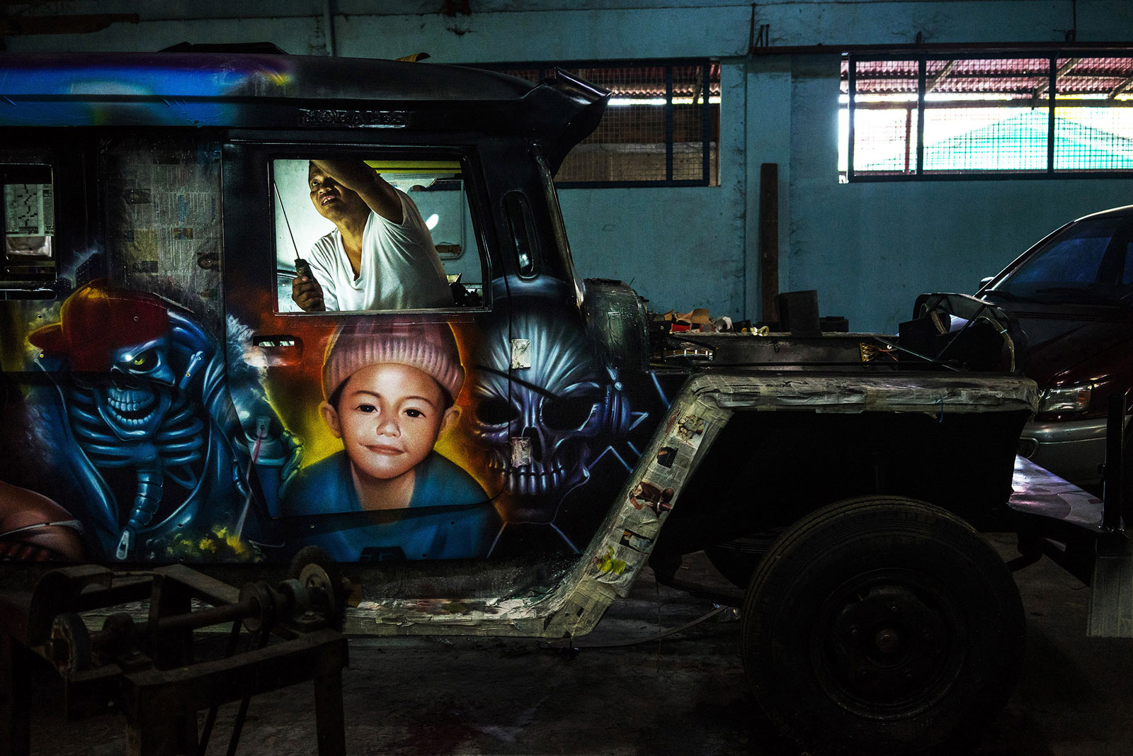 A mechanic works on the interior of a jeepney at the Morales Motors workshop in San Mateo, Rizal Province, the Philippines