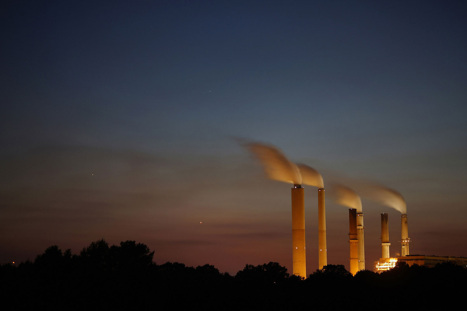 Emissions rise from stacks at the Duke Energy Gibson Station power plant at dusk in Owensville, Ind., U.S.