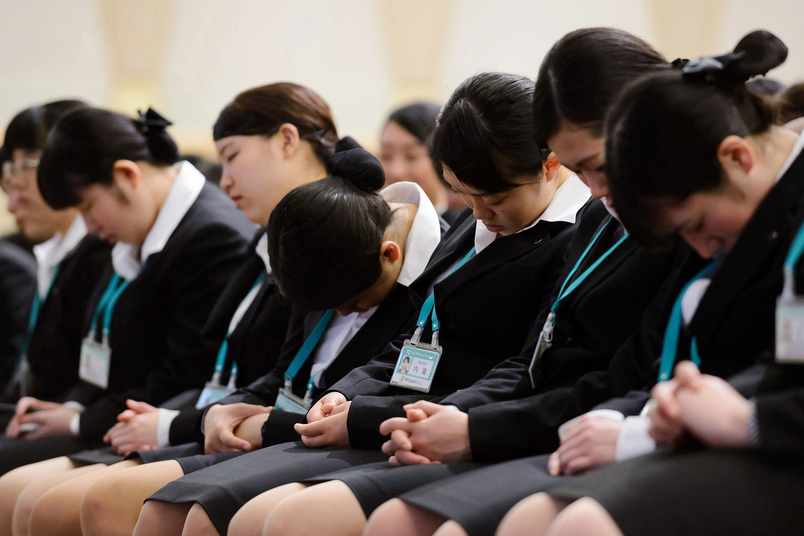 New Employees of Seven & I Holdings rest during an intermission of an initiation ceremony in Tokyo on Thursday, March 19, 2015.