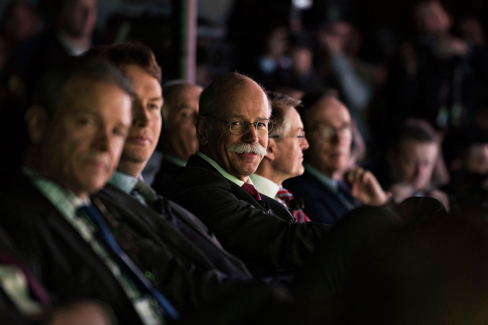 Dieter Zetsche, chief executive officer of Daimler, reacts while sitting in the audience during a Mercedes-Benz event ahead of the 2015 North American International Auto Show in Detroit