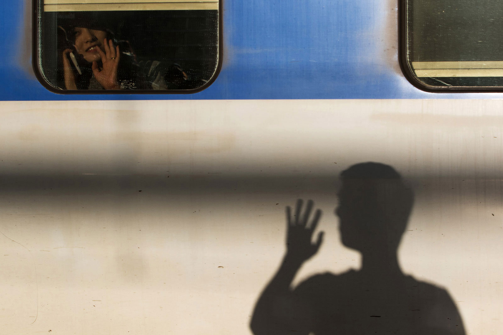 A woman sitting inside a Korea Train Express bullet train waves her hand as the shadow of a man is cast on the side of the train at Seoul Station