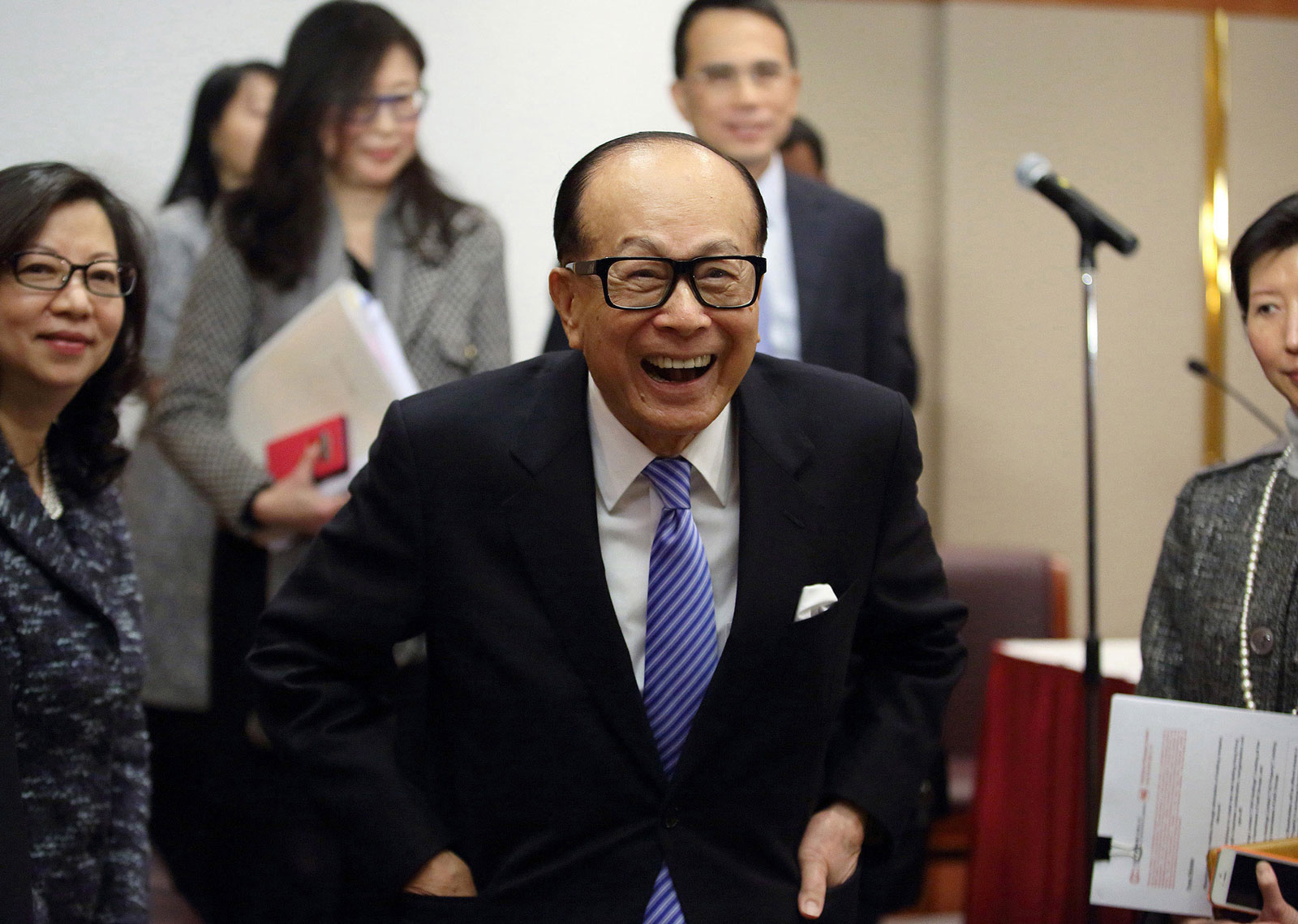 Billionaire Li Ka-shing, chairman of Cheung Kong Holdings and Hutchison Whampoa, reacts while speaking to the media as he leaves a news conference in Hong Kong