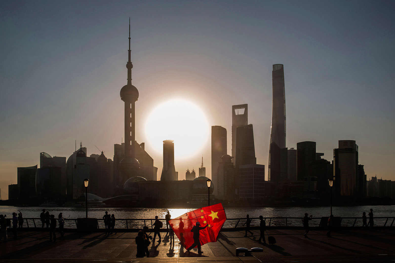 A man carrying a Chinese national flag kite walks along the Bund in Shanghai