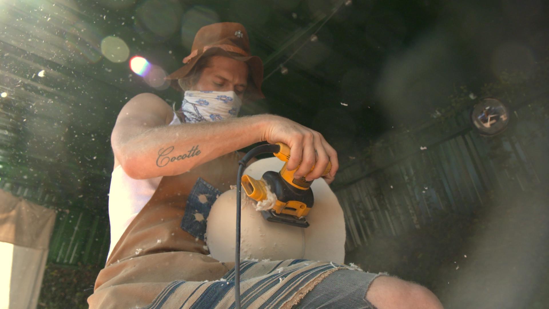 Nick Fouquet uses an electric sander to shape a felt hat. 7fc037a6db04