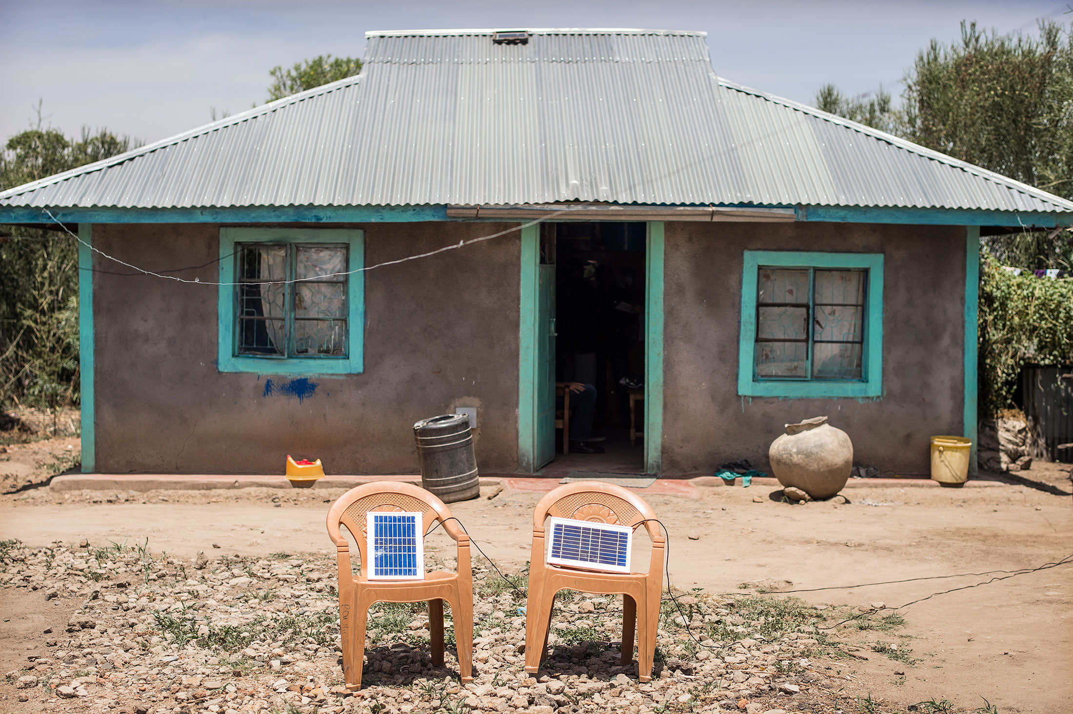 Solar panels charging a light system outside a house in a rural area ...