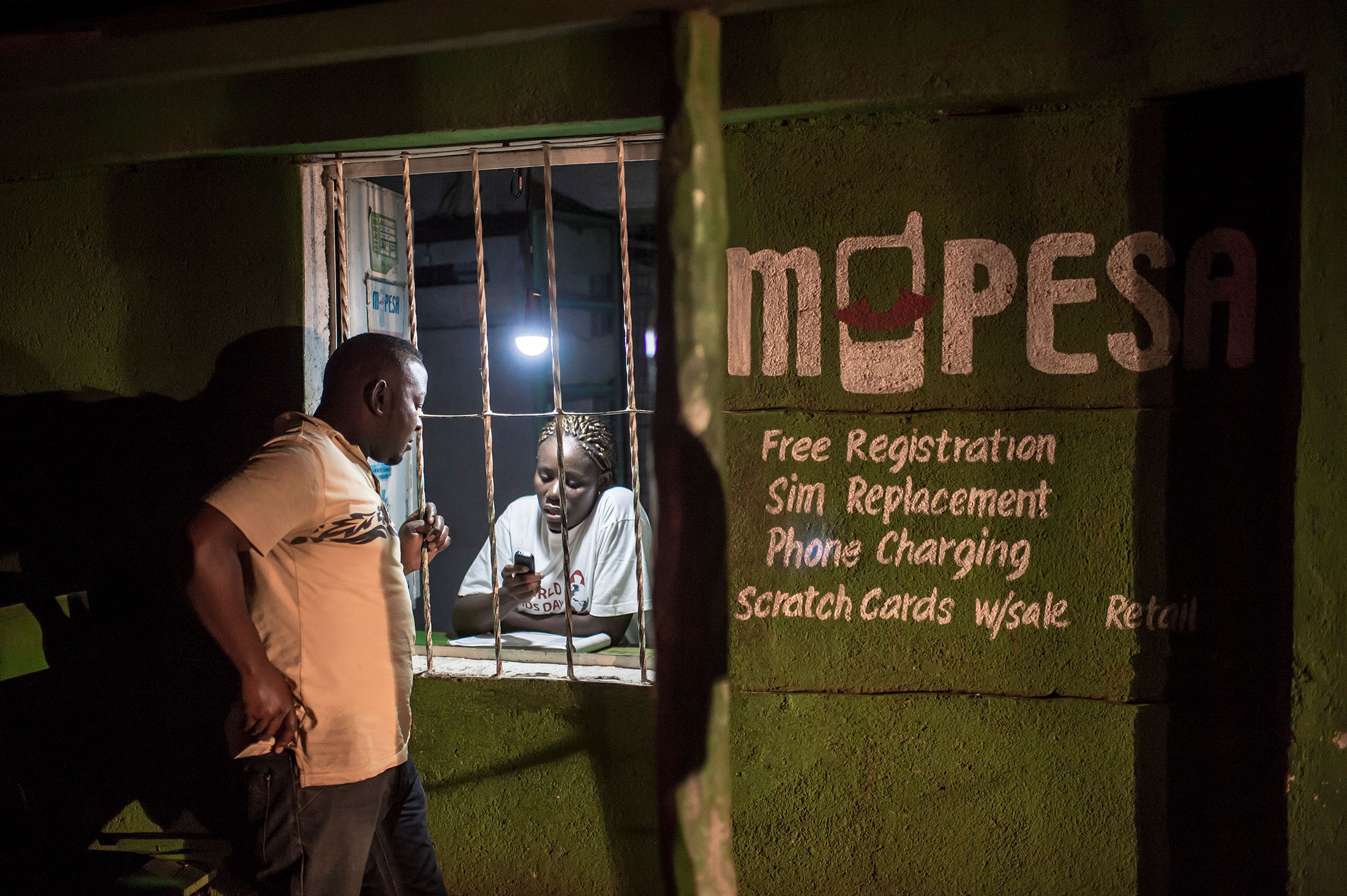 An M-Pesa agent in Kisumu helping a customer.