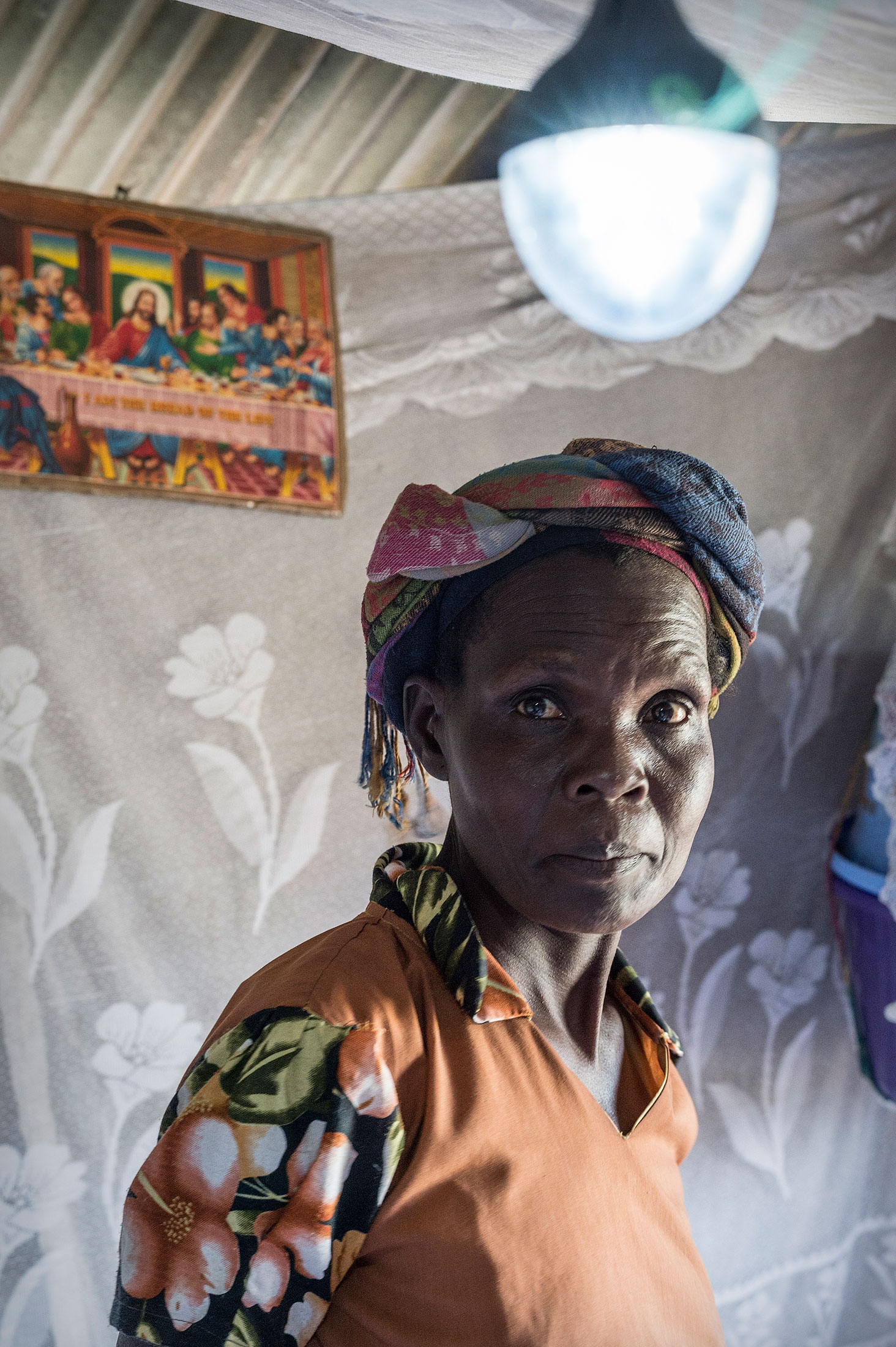 A customer, Susan Atieno, in her house with solar lights.