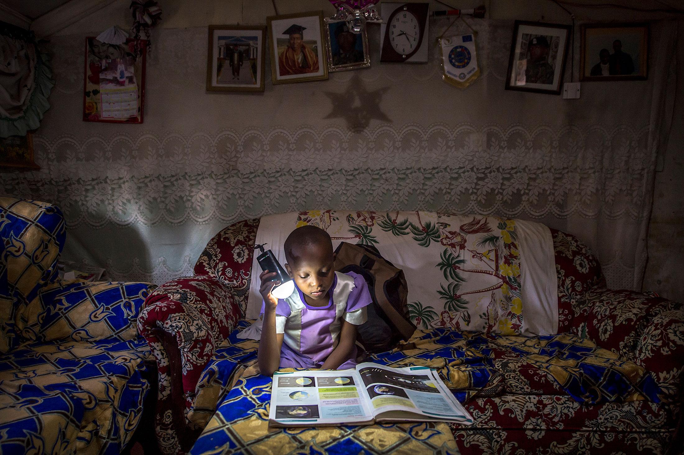 A Nairobi schoolgirl studying at night.