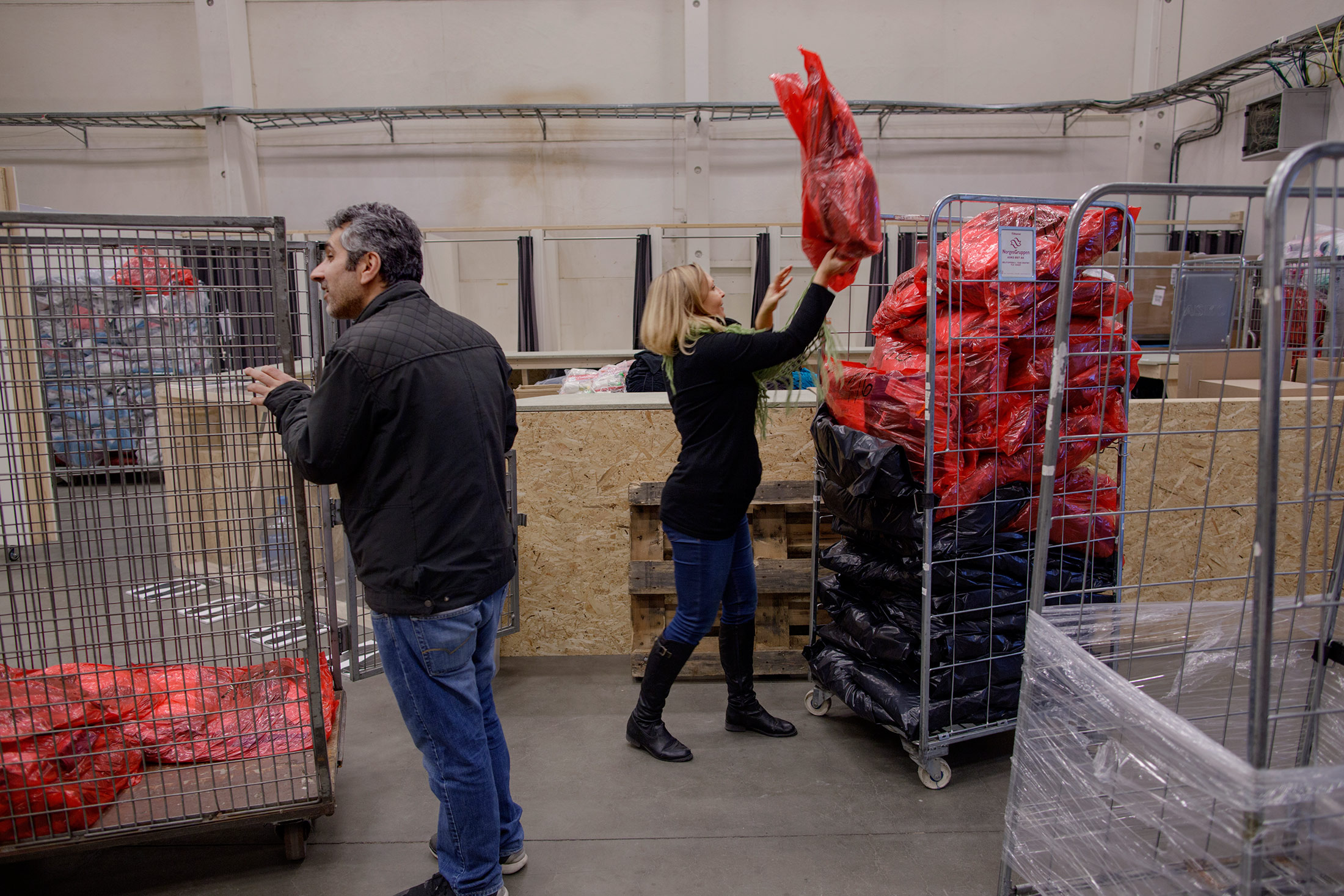 Adnan Mousa, responsible for the stock of clothing at Rade, and Kari-Anne Andersen, community worker at Hero, organize clothing that is handed out to newly arrived refugees.