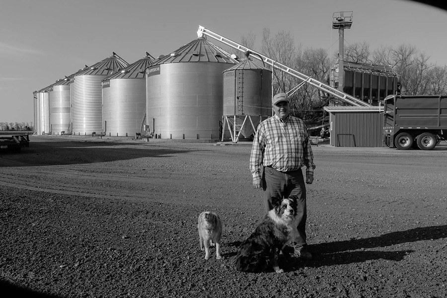 Kevin Skunes with his dogs, Jack and Ike, in front of bins full of corn.