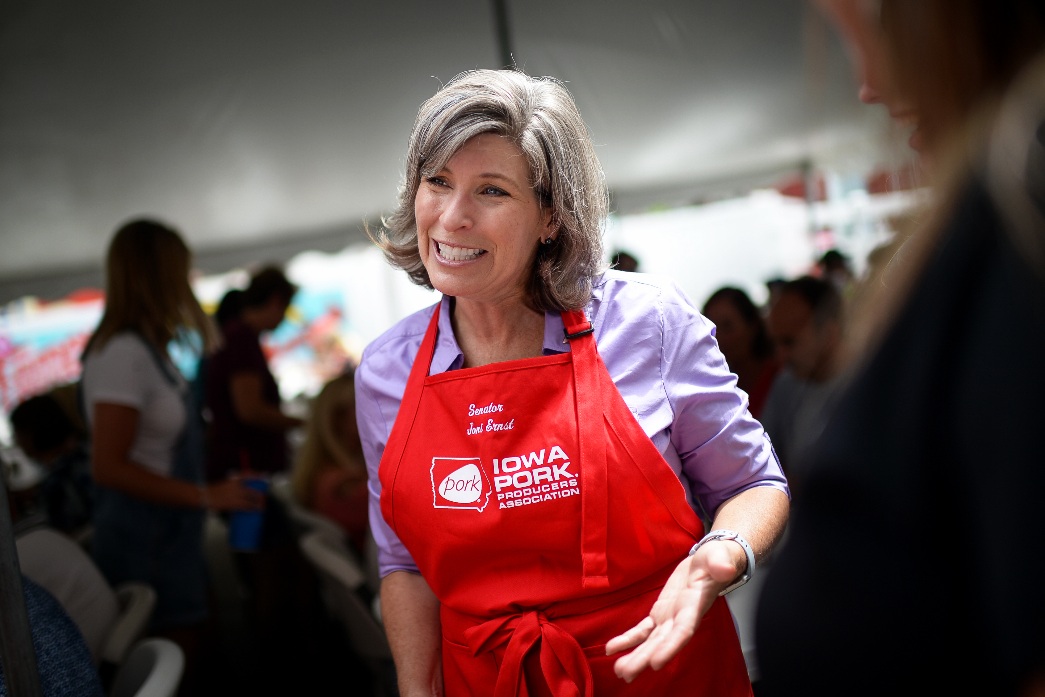 Sen. Joni Ernst talks with fairgoers as she works at the Pork Tent at the Iowa State Fair on Saturday August 17, 2019.
